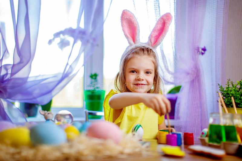 Happy easter girl in bunny ears painting eggs, small child at home. spring holiday. Colorful painted eggs, flowers in vase. Happy easter girl in bunny ears royalty free stock image