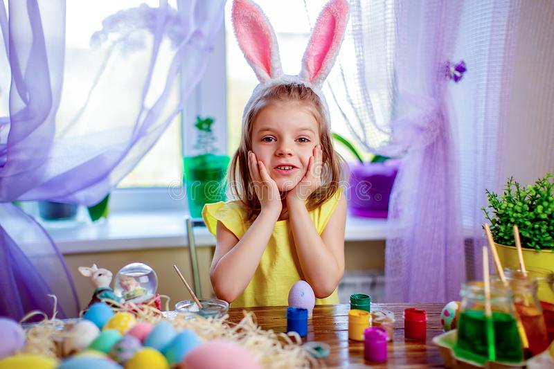 Happy easter girl in bunny ears painting eggs, small child at home. spring holiday. Colorful painted eggs, flowers in vase. Happy easter girl in bunny ears stock photo