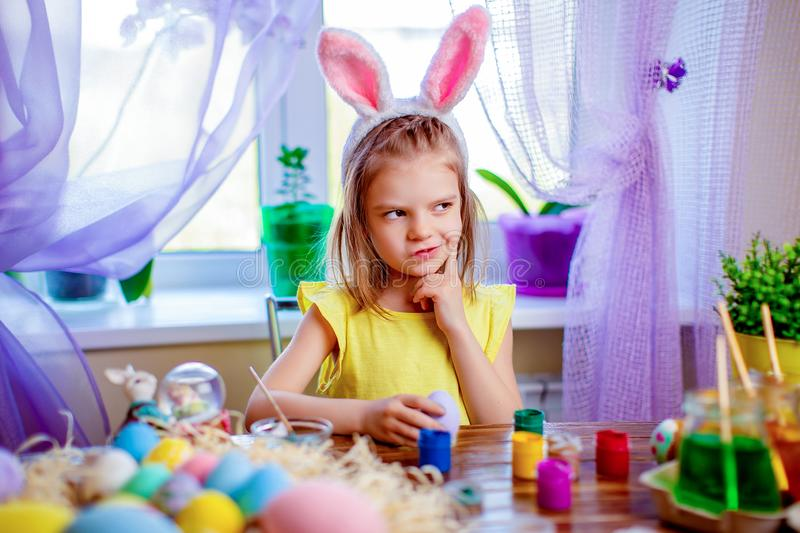 Happy easter girl in bunny ears painting eggs, small child at home. spring holiday. Colorful painted eggs, flowers in vase. Happy easter girl in bunny ears stock photos