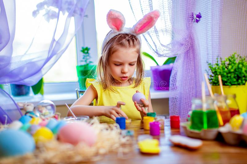 Happy easter girl in bunny ears painting eggs, small child at home. spring holiday. Colorful painted eggs, flowers in vase. Happy easter girl in bunny ears stock images