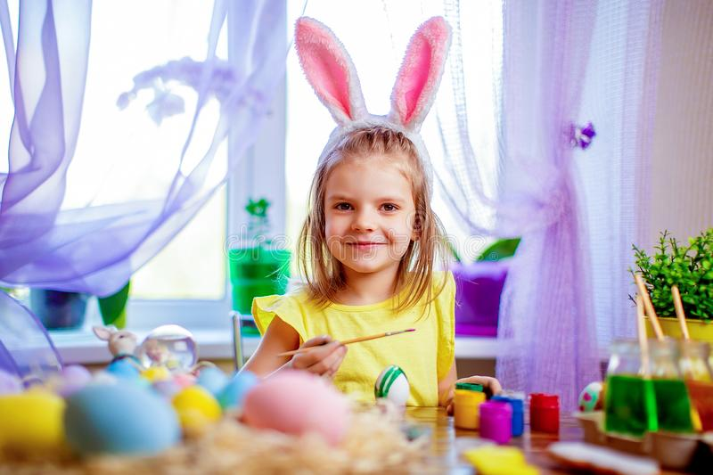 Happy easter girl in bunny ears painting eggs, small child at home. spring holiday. Colorful painted eggs, flowers in vase. Happy easter girl in bunny ears royalty free stock photo