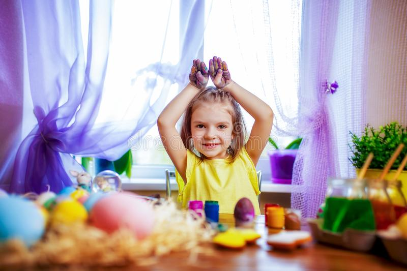 Happy easter girl in bunny ears painting eggs, small child at home. spring holiday. Colorful painted eggs, flowers in vase. Happy easter girl making bunny ears stock image