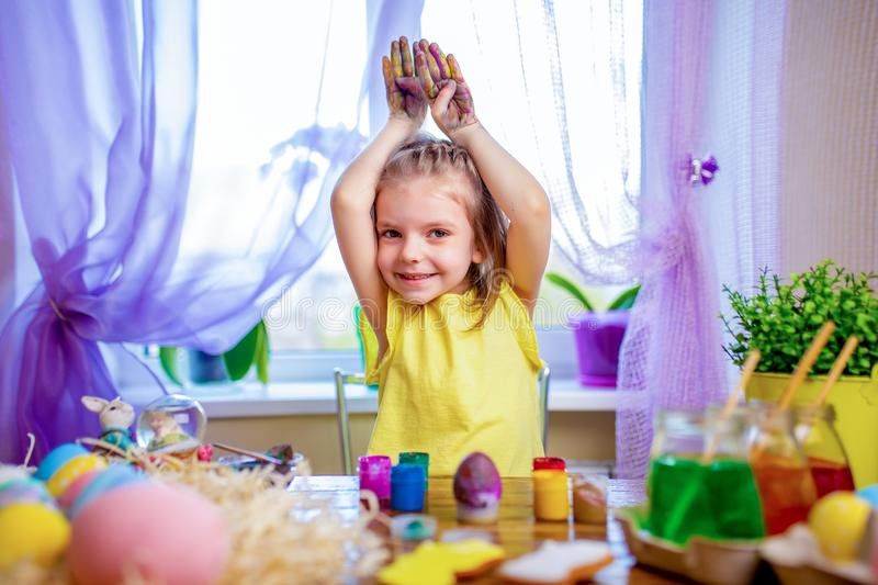 Happy easter girl in bunny ears painting eggs, small child at home. spring holiday. Colorful painted eggs, flowers in vase. Happy easter girl making bunny ears royalty free stock images