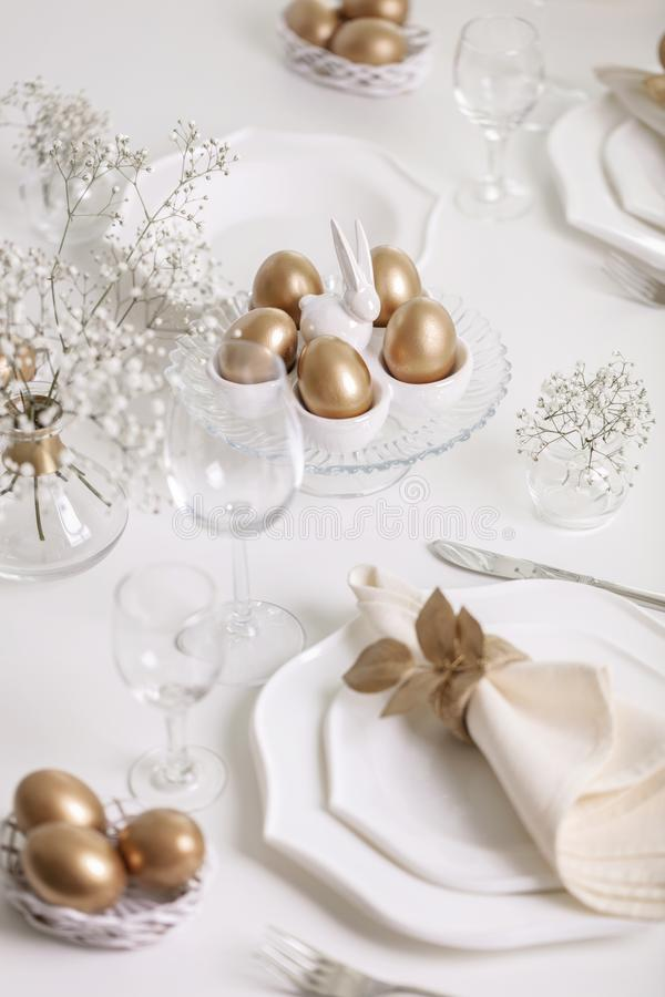 Happy Easter! Golden decor and table setting of the Easter table with white dishes of white color stock photography