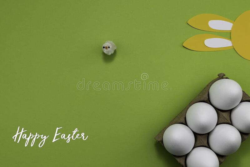 Happy Easter with eggs and paper bunny ears on a green background. royalty free stock image