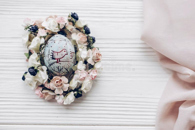 Happy easter greeting card. easter egg with chick ornaments in f. Loral nest with flowers on rustic white wooden desk background. space for text, top view. soft stock photography