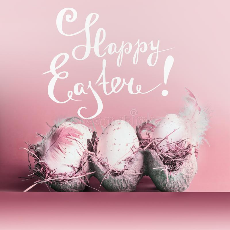 Happy Easter greeting card with eggs in grate with feathers  at pastel pink background and lettering royalty free stock images