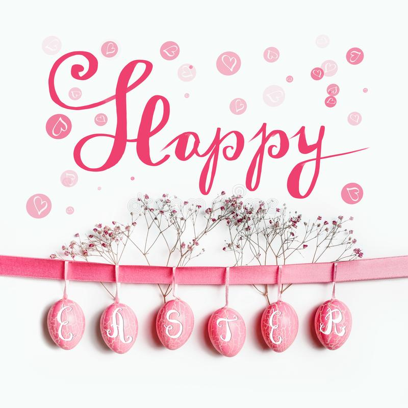 Happy Easter greeting card lettering with hanging pastel pink Easter eggs on ribbon with flowers at white wall background royalty free stock photo