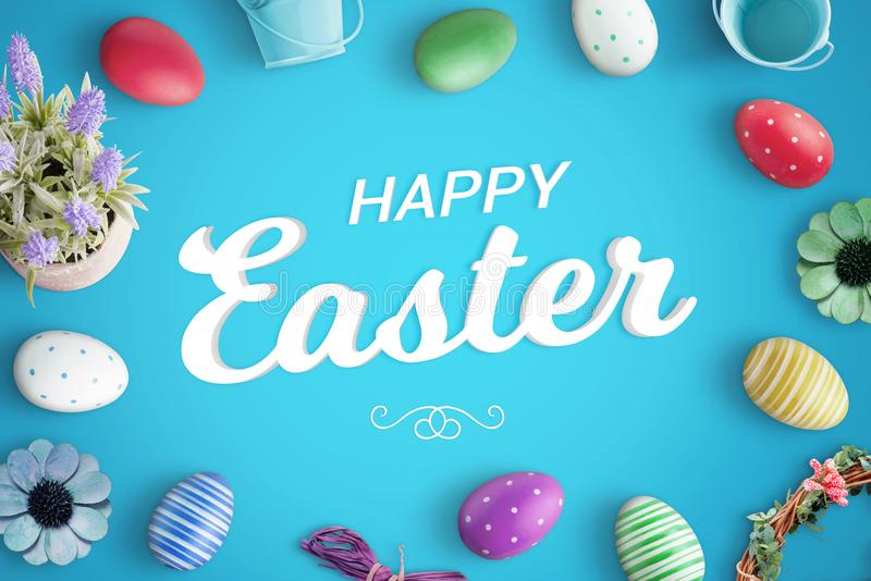 Happy Easter greeting text on blue background surrounded with colorful eggs and decorations royalty free stock photography
