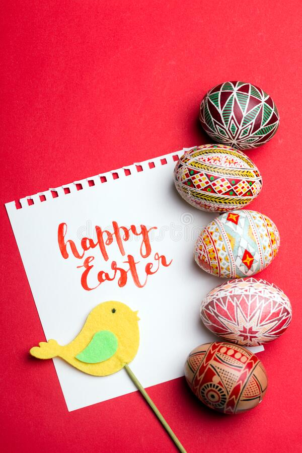 The happy easter. Happy easter card. beautiful Easter egg Pysanka handmade - ukrainian traditional on a red background stock image