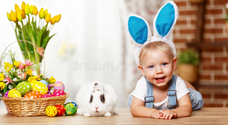 Happy easter! happy funny baby boy playing with bunny. Happy easter! happy funny baby boy playing with Easter bunny royalty free stock photography