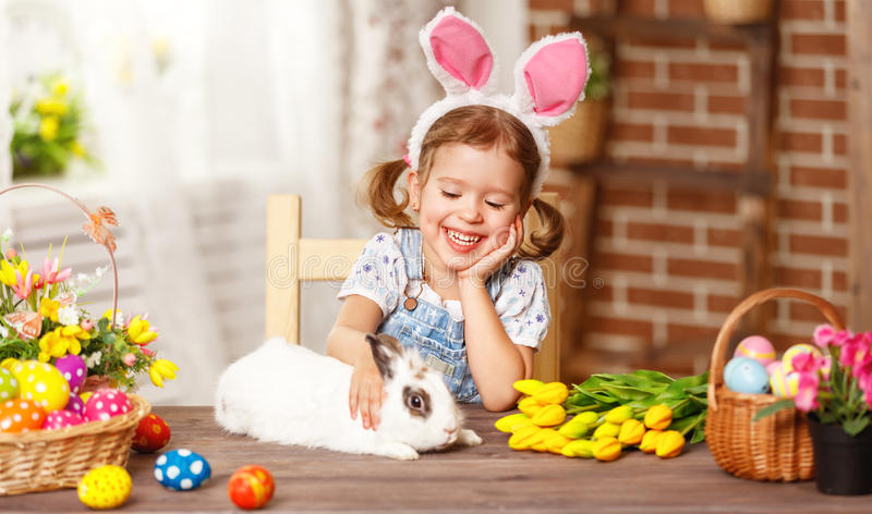Happy easter! happy funny child girl playing with bunny. Happy easter! happy funny child girl playing with Easter bunny royalty free stock photography
