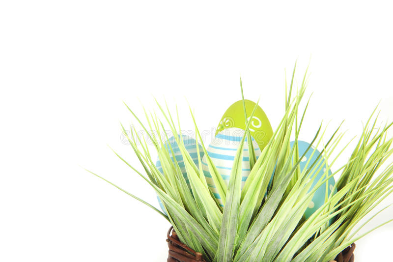 Happy Easter inscription - few eggs on the wooden basket with a grass on the white background stock images