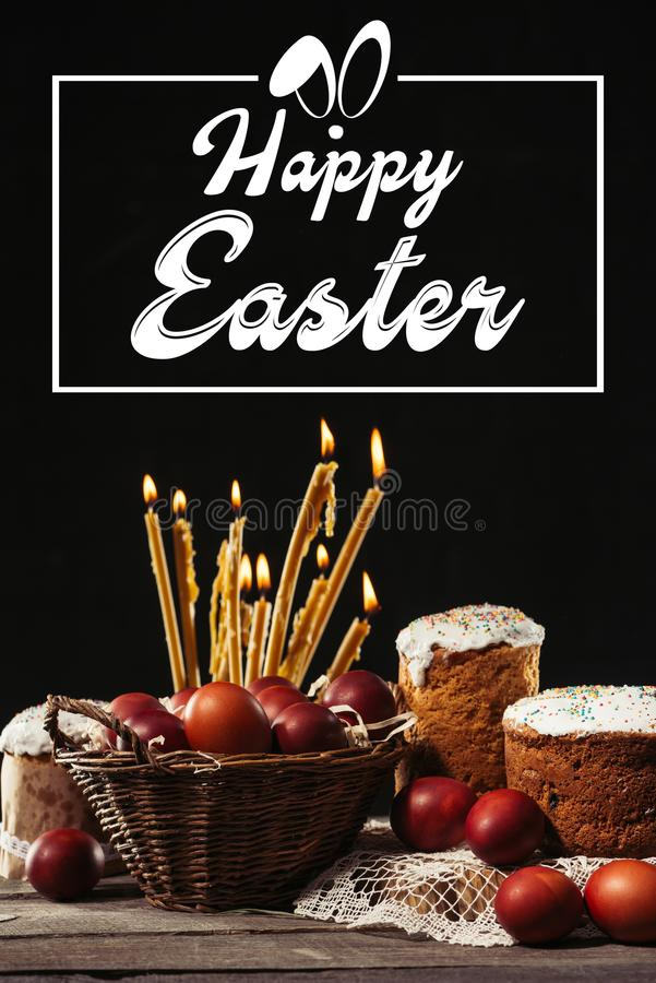 Happy easter inscription in frame, burning candles, easter cakes and painted eggs. On black stock images