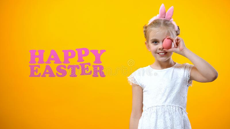 Happy Easter inscription, playful girl holding colored egg in front of her eye royalty free stock photography