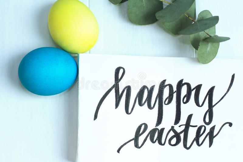 Happy Easter inscription, yellow and blue eggs on a white wooden background royalty free stock photos