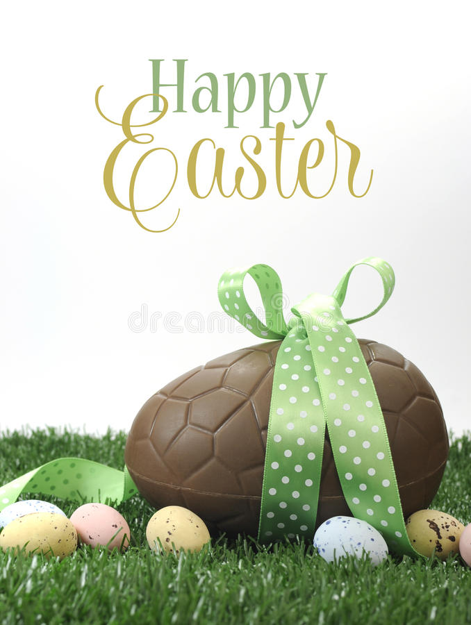 Happy Easter large chocolate Easter egg with sample text. Beautiful Happy Easter large chocolate Easter egg and small candy speckled eggs on grass with sample stock images