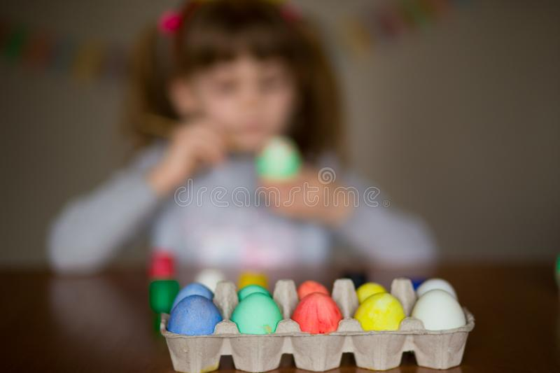 Happy easter. Little girl painter painted eggs. Kid preparing for Easter. Painted hand. Finger paint. Art and craft concept. Traditional spring holiday food stock photo