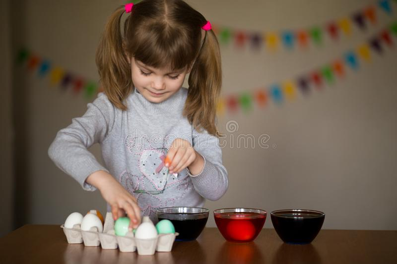 Happy easter. Little girl painter painted eggs. Kid preparing for Easter. Painted hand. Finger paint. Art and craft concept. Traditional spring holiday food royalty free stock photography