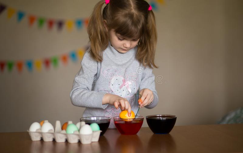 Happy easter. Little girl painter painted eggs. Kid preparing for Easter. Painted hand. Finger paint. Art and craft concept. Traditional spring holiday food stock images