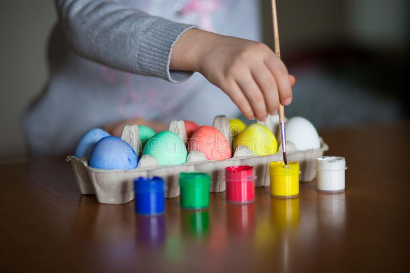 Happy easter. Little girl painter painted eggs. Kid preparing for Easter. Painted hand. Finger paint. Art and craft concept. Traditional spring holiday food stock photography