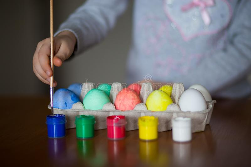 Happy easter. Little girl painter painted eggs. Kid preparing for Easter. Painted hand. Finger paint. Art and craft concept. Traditional spring holiday food royalty free stock images
