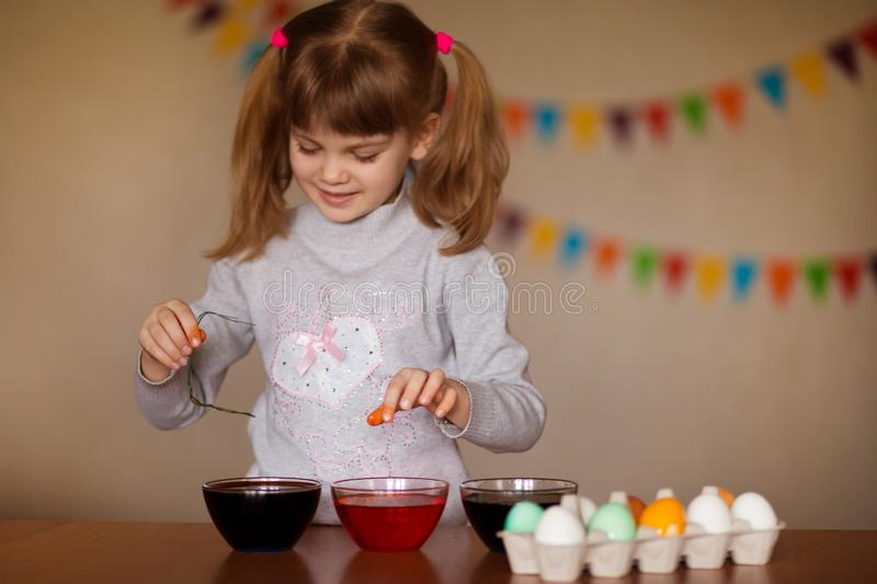 Happy easter. Little girl painter painted eggs. Kid preparing for Easter. Painted hand. Finger paint. Art and craft concept. Traditional spring holiday food royalty free stock photo