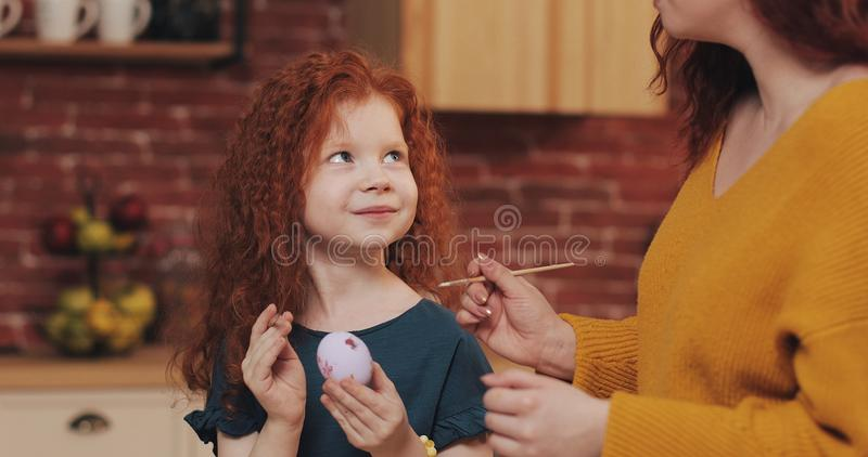 Happy easter. Mom teaches her daughter painting eggs. Happy family preparing for Easter. They wearing bunny ears royalty free stock photos