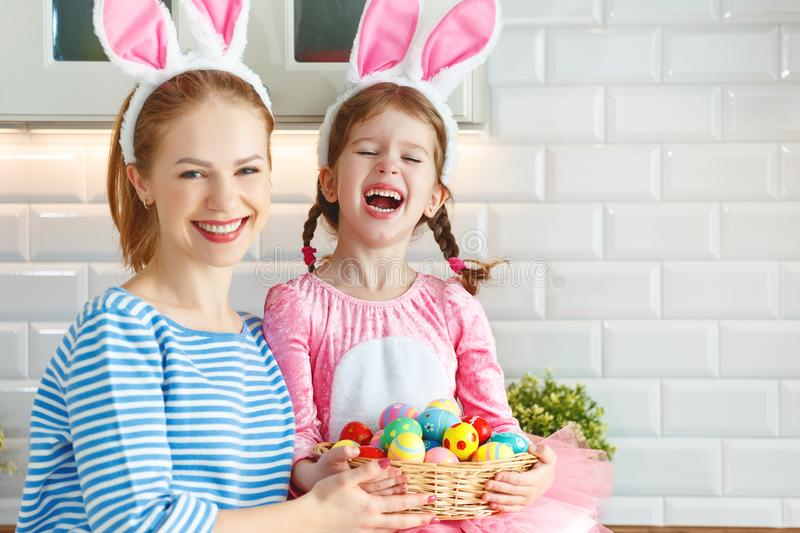 Happy easter! mother and child daughter with ears hare getting ready for holiday. Happy easter! family mother and child daughter with ears hare getting ready for royalty free stock photo