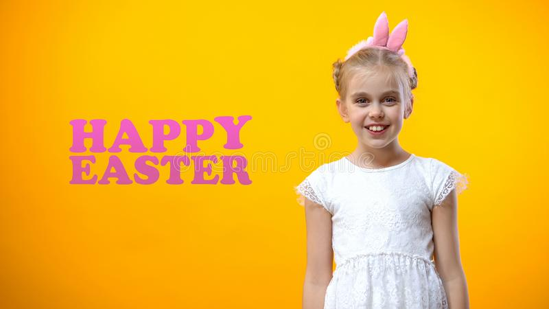 Happy Easter phrase, cute girl in bunny ears smiling to camera, greeting card stock images