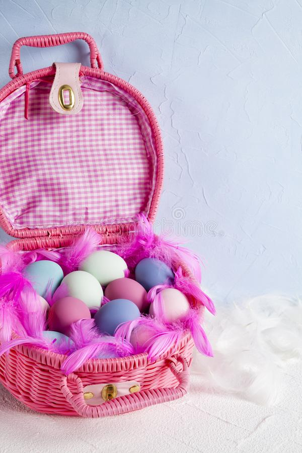 Happy Easter - pink basket full of colored eggs and feathers royalty free stock images