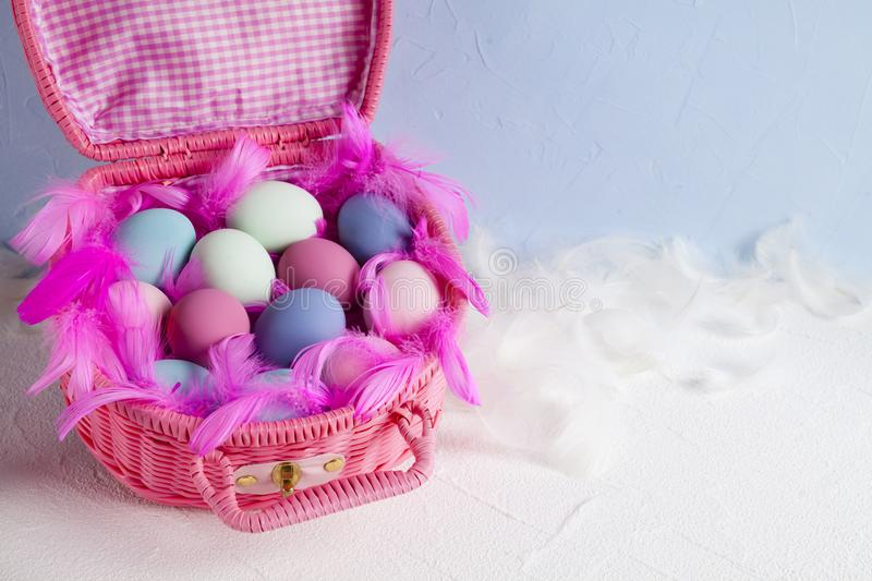 Happy Easter - pink basket full of colored eggs and feathers stock photography