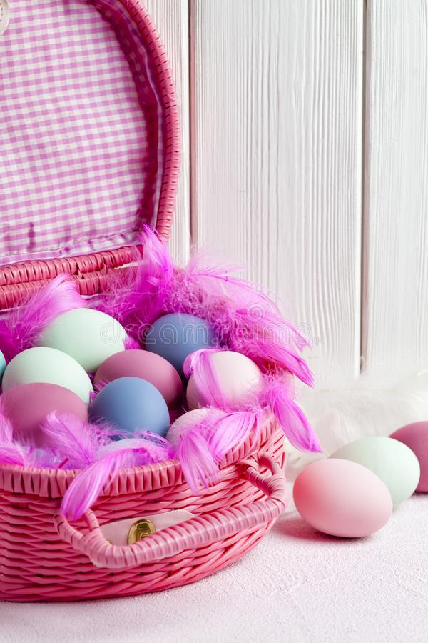 Happy Easter - pink basket full of colored eggs and feathers stock images