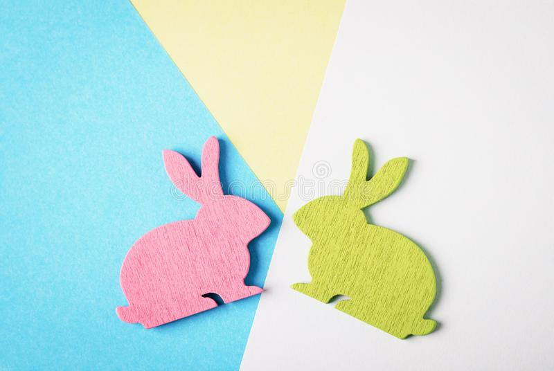 Happy Easter. Pink and green wooden Easter bunny on a blue and white and yellow background. Trendy creative photo stock image