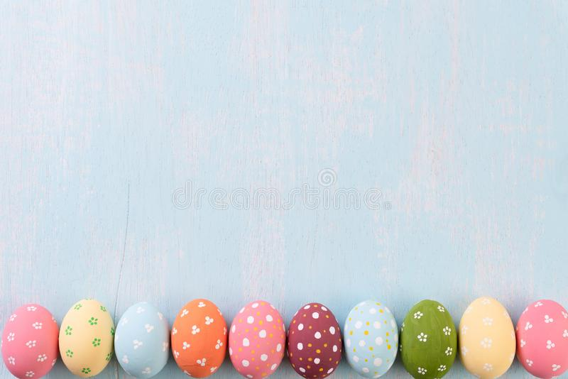 Happy easter! Row Easter eggs on bright blue wooden background royalty free stock images