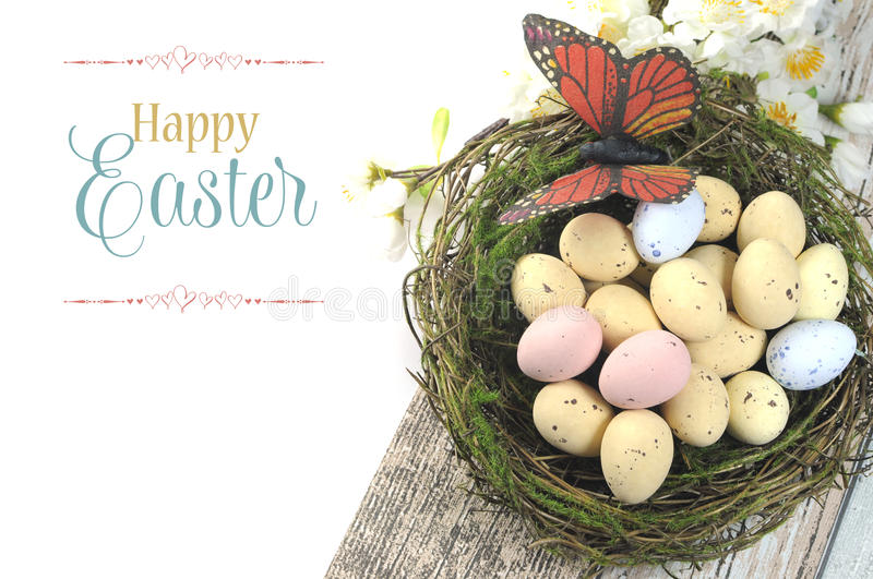 Happy Easter shabby chic table with speckled birds eggs and butterfly in nest. With spring blossoms and sample text or copy space for your text here royalty free stock images