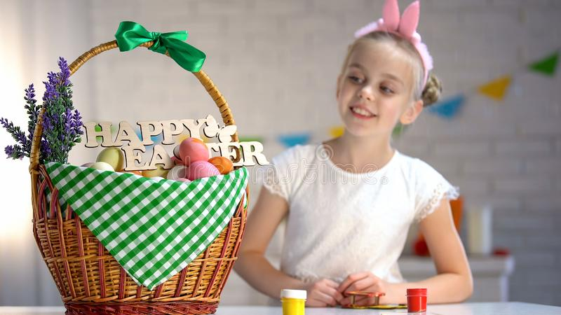 Happy Easter sign on basket, pretty girl looking at big basket full of dyed eggs royalty free stock photography
