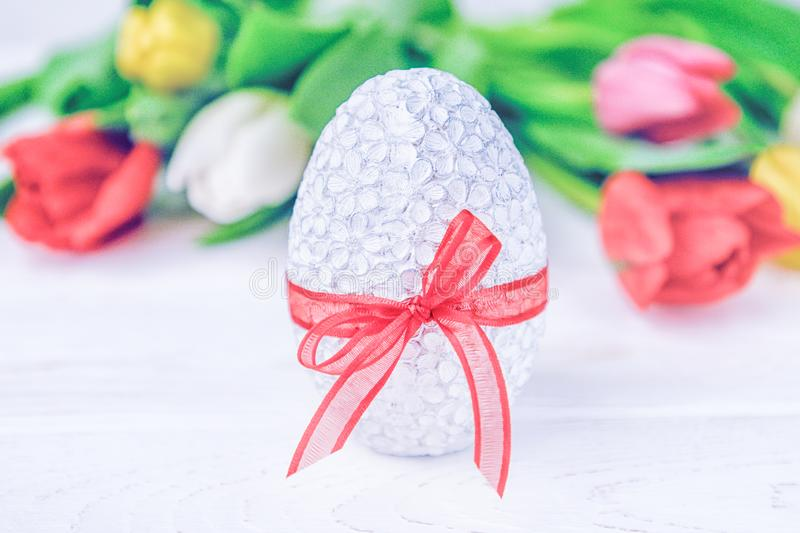 Happy Easter. Easter egg and colorful tulips on a white background royalty free stock images