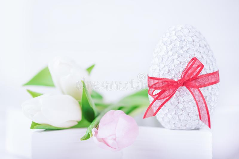 Happy Easter. Easter egg and delicate tulips on a white background. Copy space royalty free stock photo