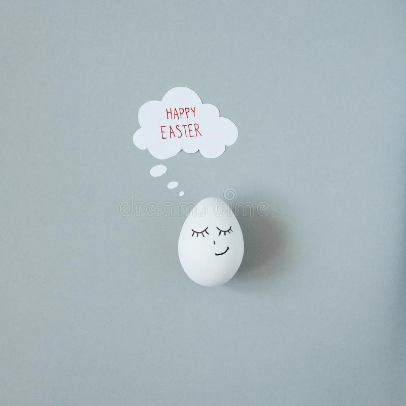 Happy Easter. Smiling easter egg with thought bubble on gray background stock images