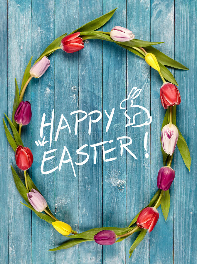 Happy Easter spring frame of fresh tulips. Happy Easter spring frame or oval wreath of fresh colorful tulips on blue wooden boards with a central greeting and royalty free stock photo