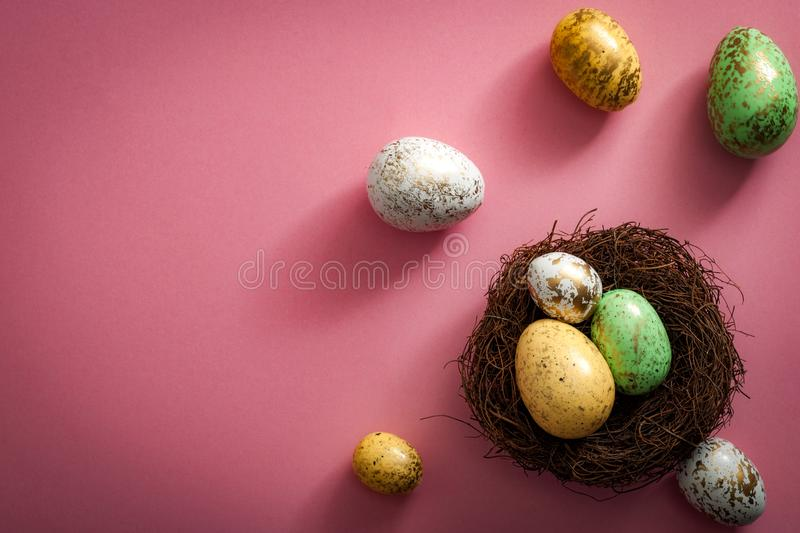 Happy easter and spring meme concept with a colorful image of easter eggs dyed white, green and yellow with gold spots in bird stock photography