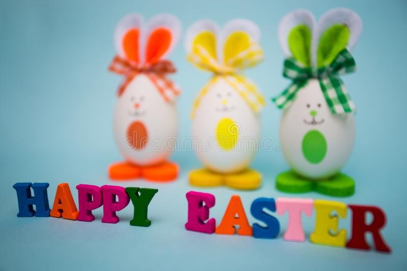 Happy easter text from colorful wooden letters with funny eggs in the form of cute bunny on blue background royalty free stock photos