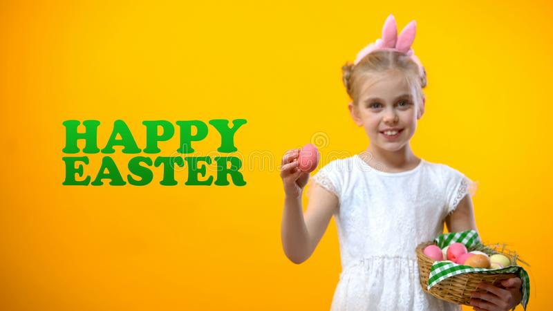 Happy Easter text, cute schoolgirl showing pink egg from basket greeting card royalty free stock photos