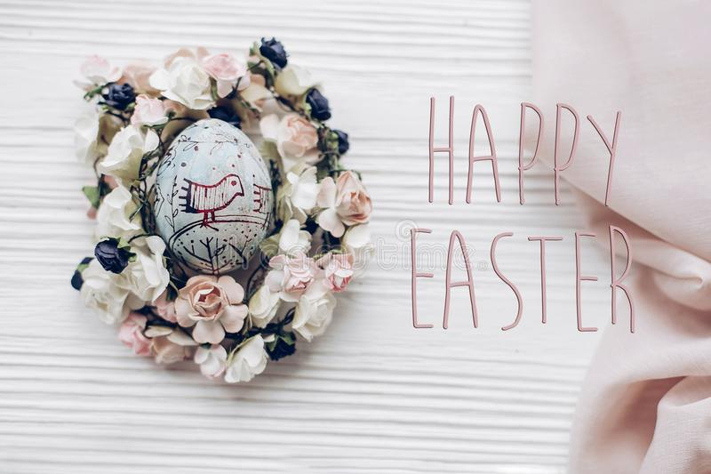 Happy easter text greeting card sign on easter egg with chick o. Rnaments in floral nest with flowers on rustic white wooden desk background. space for text, top royalty free stock photography