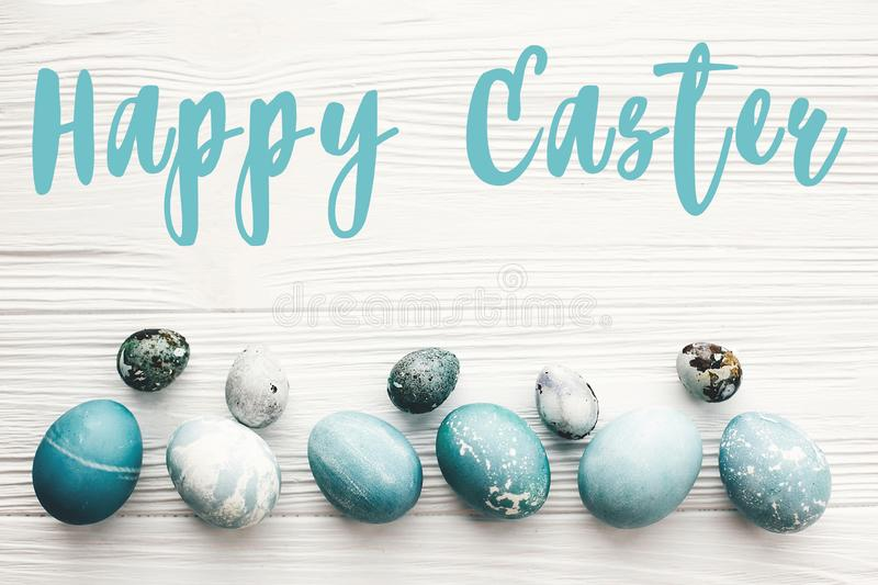 Happy Easter text sign on stylish easter eggs on white wooden table, flat lay. Modern easter eggs painted with natural dye in blue. Marble color. Easter royalty free illustration