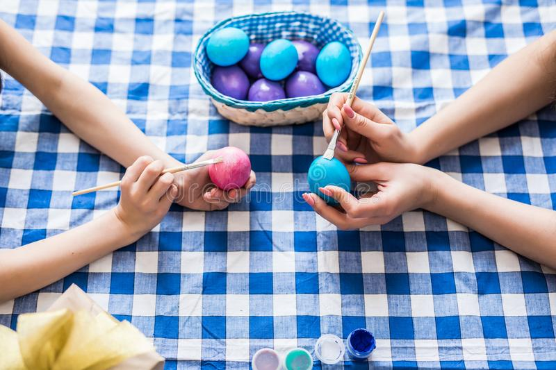 Happy easter. Top view of hands mother their daughter painting Easter eggs. Happy family preparing for Easter. royalty free stock photo