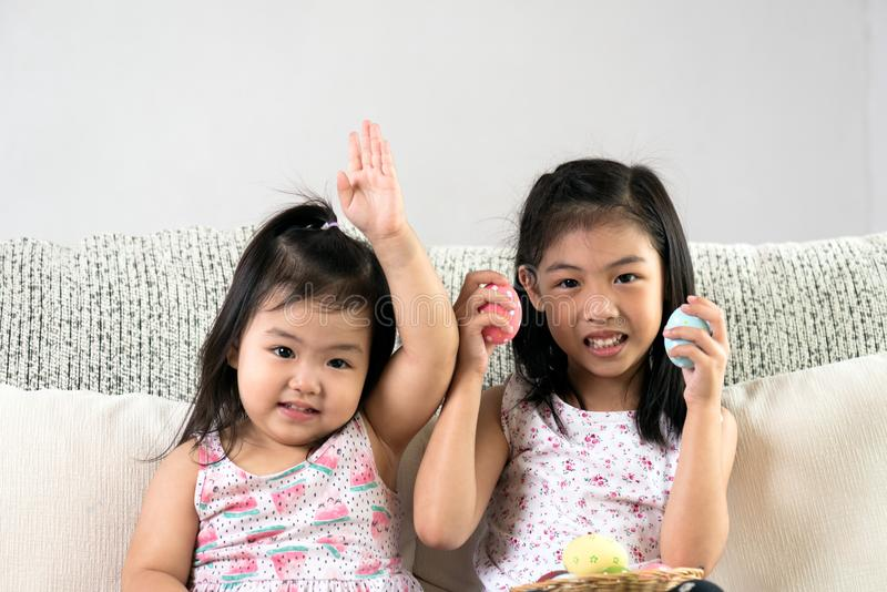 Happy easter! Two cute little children sitting on sofa with Easter eggs in the nest or basket royalty free stock images
