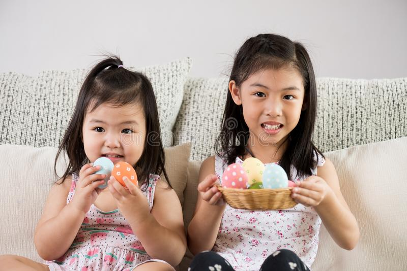 Happy easter! Two cute little children sitting on sofa with Easter eggs in the nest or basket stock image