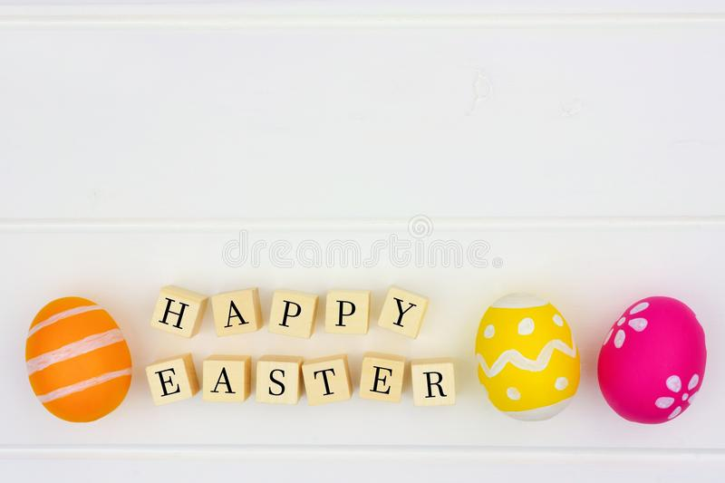 Happy Easter wooden blocks with Easter eggs against white wood stock photography
